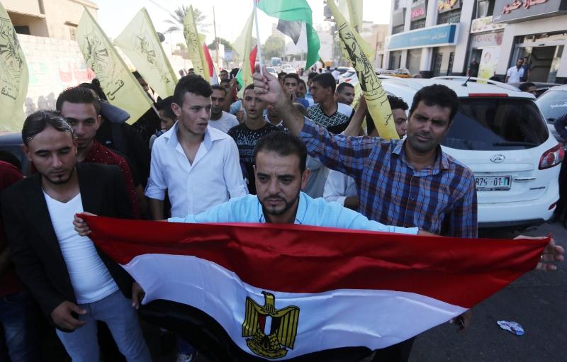 متظاهر مناصر لدحلان يحمل راية مصر خلال مسيرة في غزة (آي بي ايه)