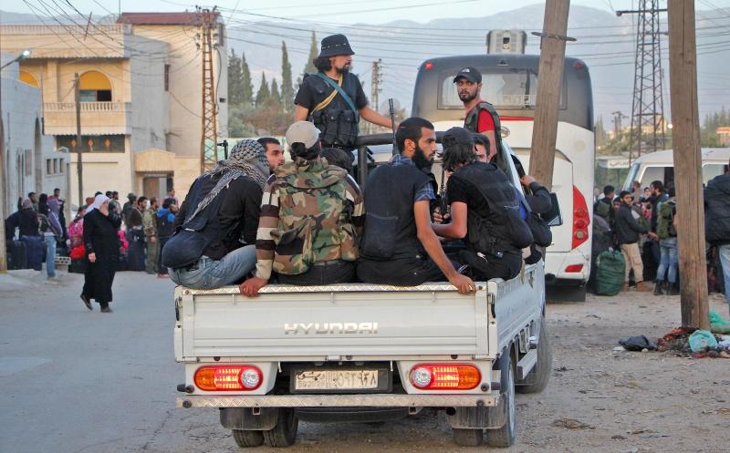 مسلحون يصلون إلى إدلب إثر بدء تطبيق اتفاق المصالحة في الهامة وقدسيا (أ ف ب)