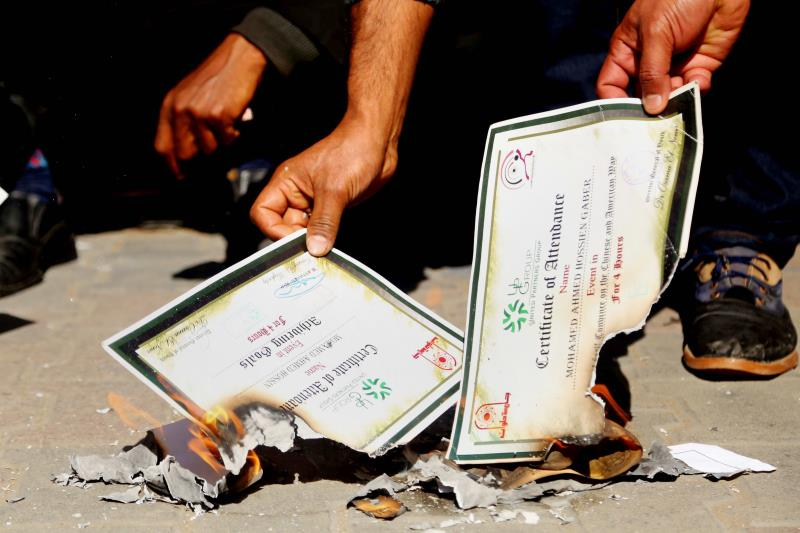 مجموعة من حملة شهادات الدراسات العليا يحرقون شهاداتهم في القاهرة