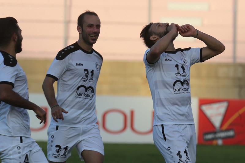 لاعب النجمة خالد تكه جي يحتفل بهدفه مع محمد حمود وحسن العمري