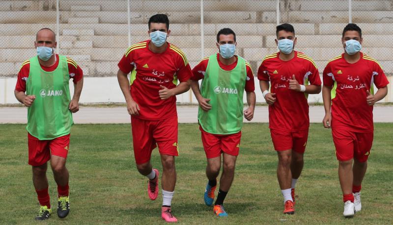 لاعبو الاجتماعي يضعون الكمامات خلال الاحماء بسبب روائح النفايات في برج حمود (عدنان الحاج علي)