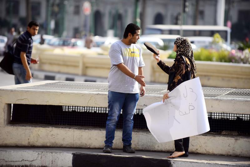 مواطنة مصرية تعترض على شاب يرفع لافتة «عواد باع أرضه» في القاهرة (آي بي ايه)