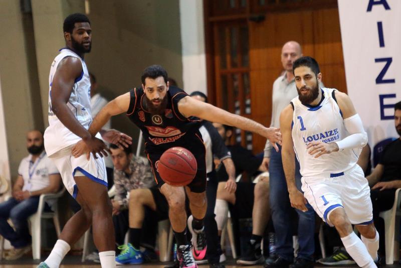 لاعب هومنتمن أحمد ابراهيم يحاول الوصول الى الكرة بمضايقة دفاعية من اللويزة (سركيس يريتيسيان)