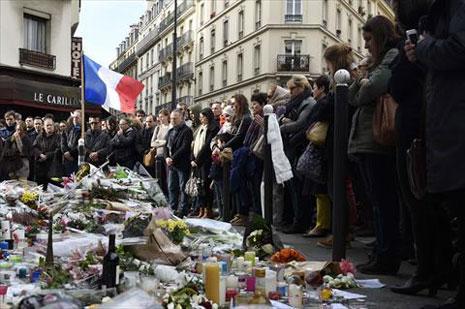 فرنسيون يقفون أمام أحد مواقع الهجمات في باريس في تشرين الثاني الماضي (أ ف ب)