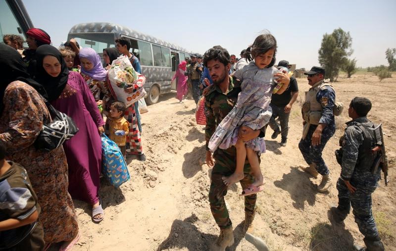 جندي عراقي يساعد المدنيين الذين هربوا من الفلوجة (أ ف ب)