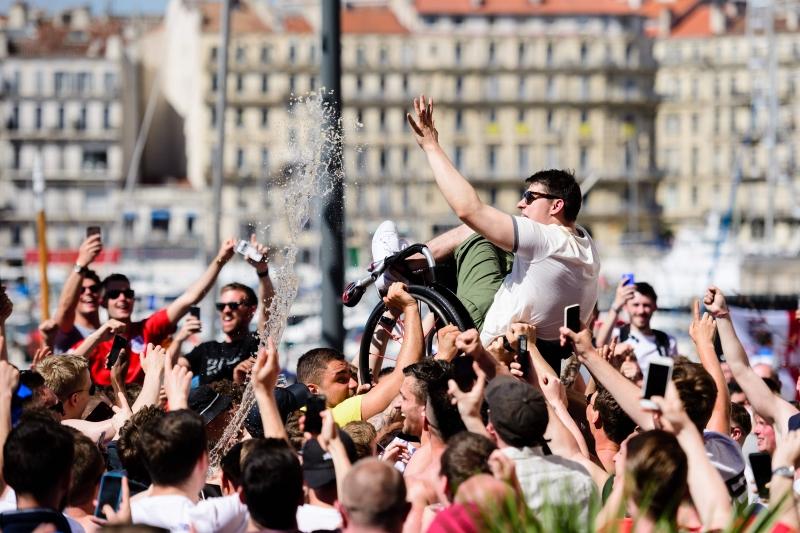 مشجعون إنكليز يرفعون زميلاً لهم على كرسي مدولب في شوارع مرسيليا أمس (ليون نيل - أ ف ب)