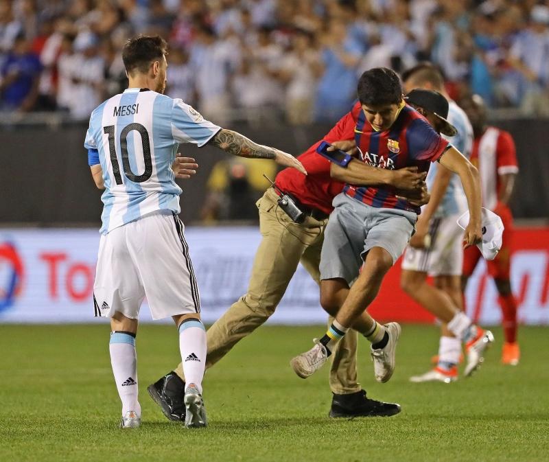رجال الأمن يحاولون منع مشجعٍ من الوصول إلى ميسي في المباراة أمام بنما (أ ف ب)