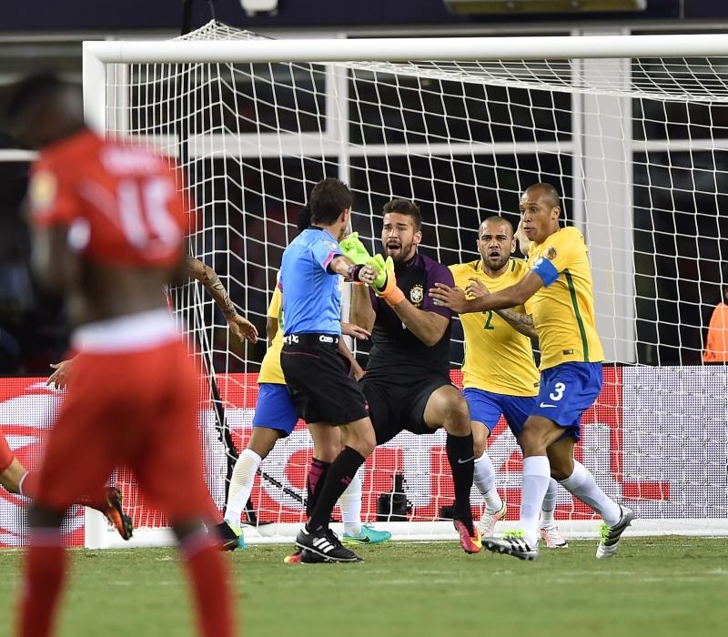 لاعبو البرازيل يعترضون على حكم المباراة بعد احتسابه هدفاً من لمسة يد للبيرو (أ ف ب)
