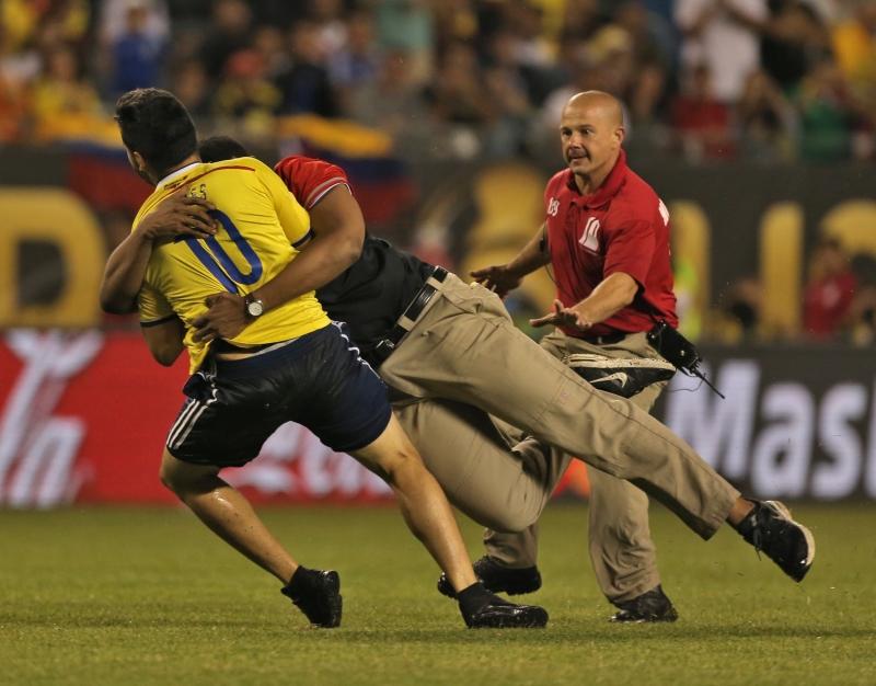 رجال الأمن يحاولون إيقاف مشجع كولومبي اقتحم الملعب (أ ف ب)