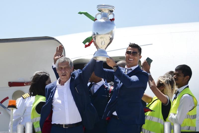 رونالدو ومدربه سانتوس يرفعان الكأس لدى الوصول الى لشبونة أمس (أ ف ب)