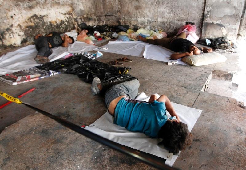 عراقيون ينامون على الأرض قرب موقع التفجير في الكرادة (أ ف ب)