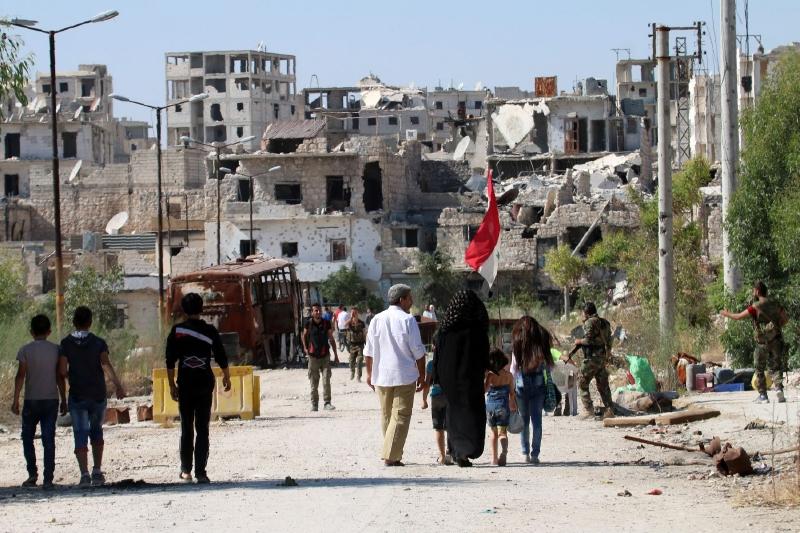عودة عدد من سكان حي بني زيد في مدينة حلب أمس (أ ف ب)