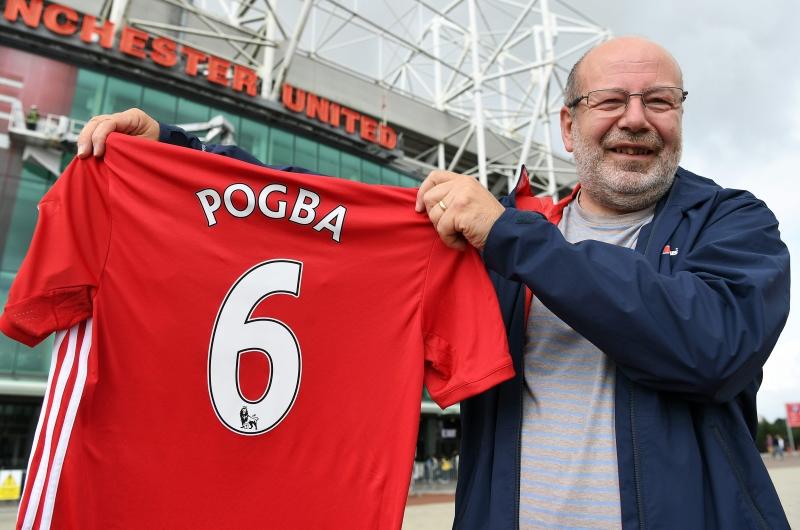 """مشجع لمانشستر يونايتد يحمل قميصاً عليه اسم ورقم بوغبا امام ملعب """"اولد ترافورد"""" (أ ف ب)"""