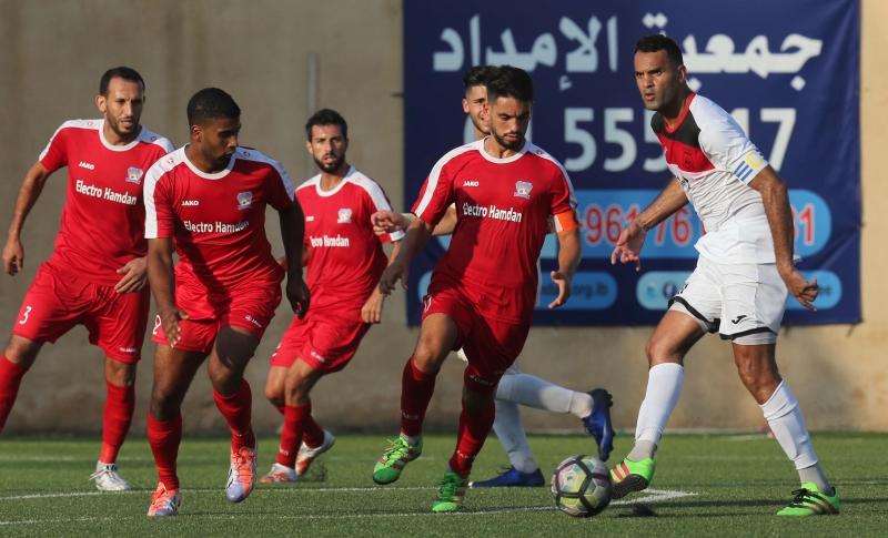 قائد التضامن رضا عنتر يمرر الكرة أمام دفاعٍ طرابلسي (عدنان الحاج علي)