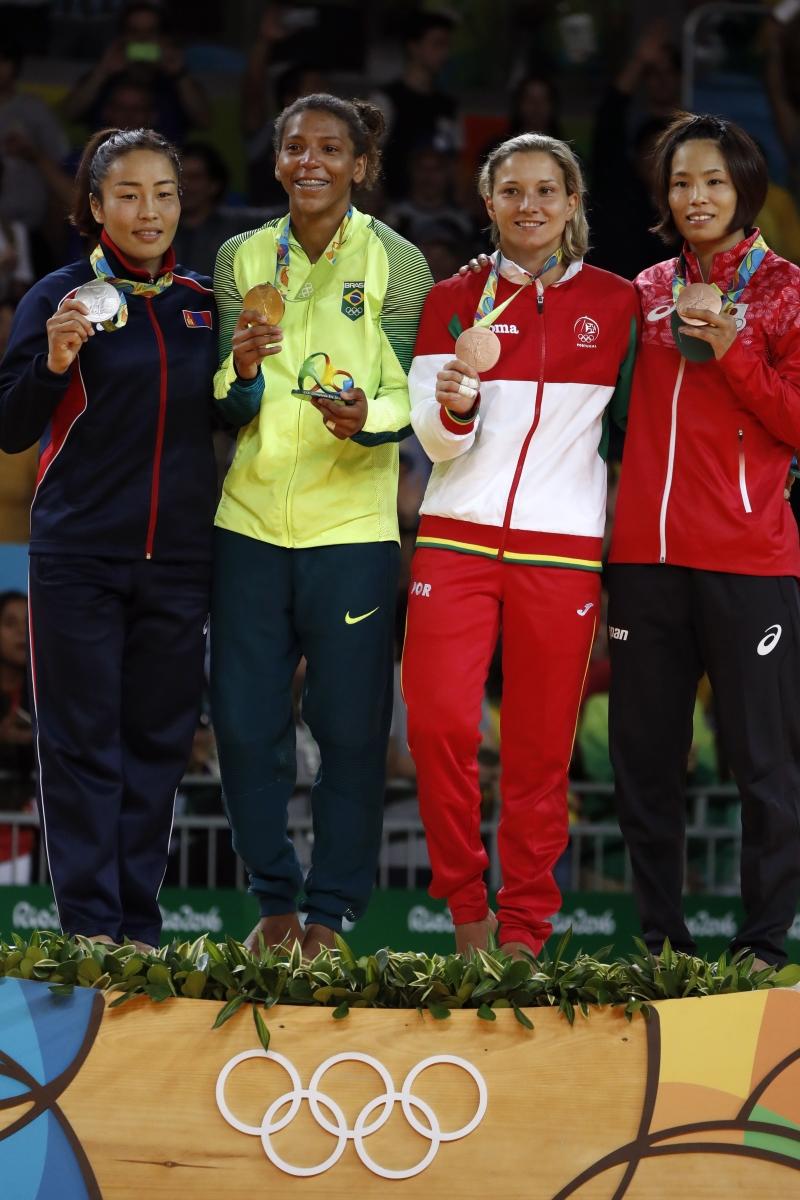 رافاييلا سيلفا تتوسط بذهبيتها المنغولية دورجسورين واليابانية ماتسوموتو (أ ف ب)