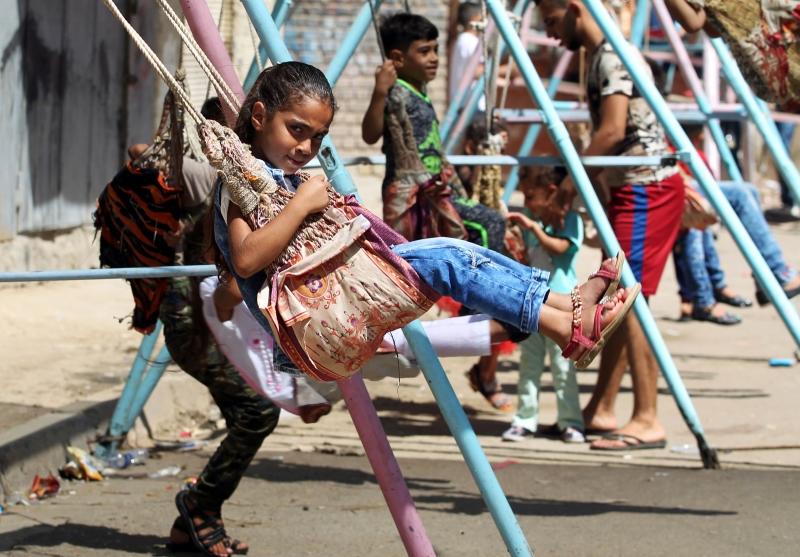 أطفال يلعبون في أحد شوارع بغداد في اليوم الأول من عيد الأضحى (أ ف ب)