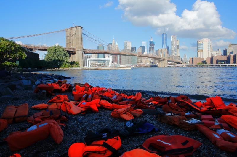 سترات نجاة استخدمها لاجئون تُعرض أمام جسر حديقة بروكلين في نيويورك قبيل قمة الأمم المتحدة (أ ف ب)