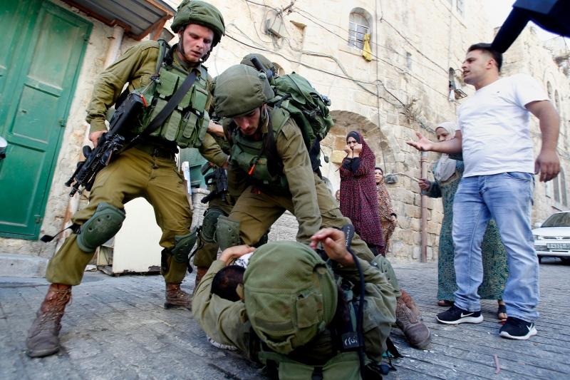 فلسطيني يطيح أرضا جنديا إسرائيليا خلال اعتقال الأول في الخليل أمس (آي بي ايه)