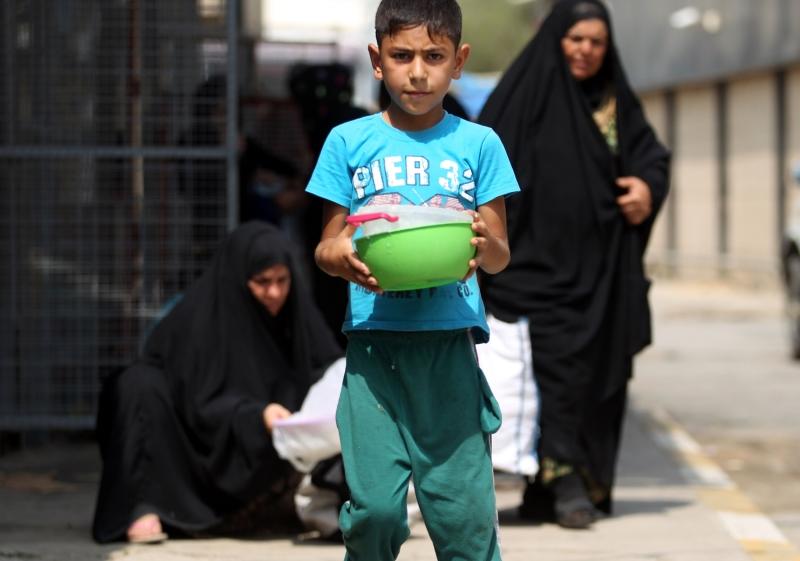 طفل نازح يحمل إناءً خلال توزيع الطعام في إحدى المناطق وسط بغداد