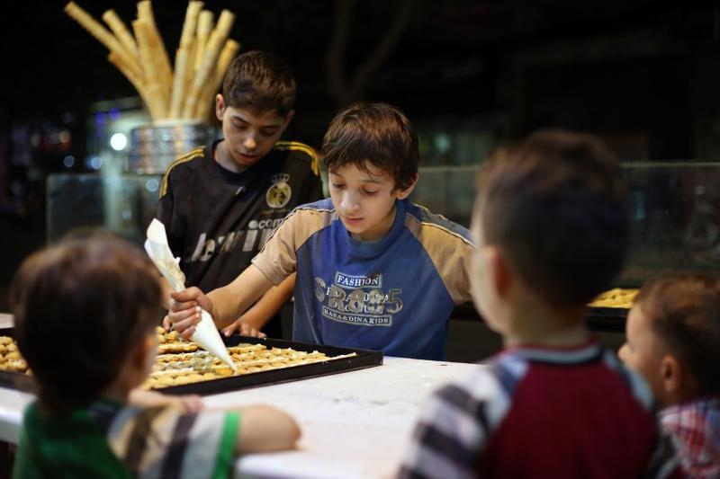 تحضير حلويات خلال عيد الفطر الماضي في معمل داخل مدينة سقبا في ريف دمشق الشرقي (أ ف ب)