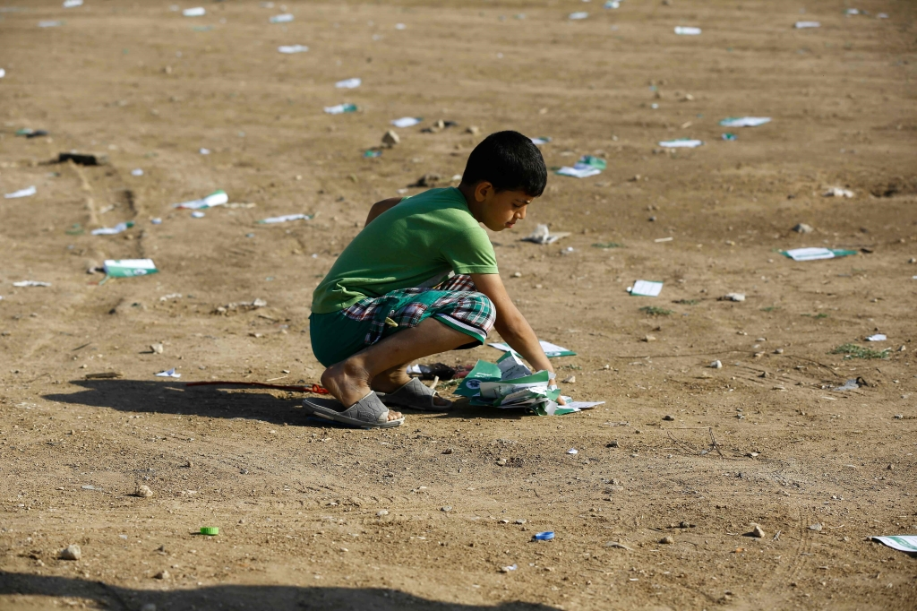 طفل فلسطيني يجمع منشورات ألقتها طائرات العدو (أ ف ب)