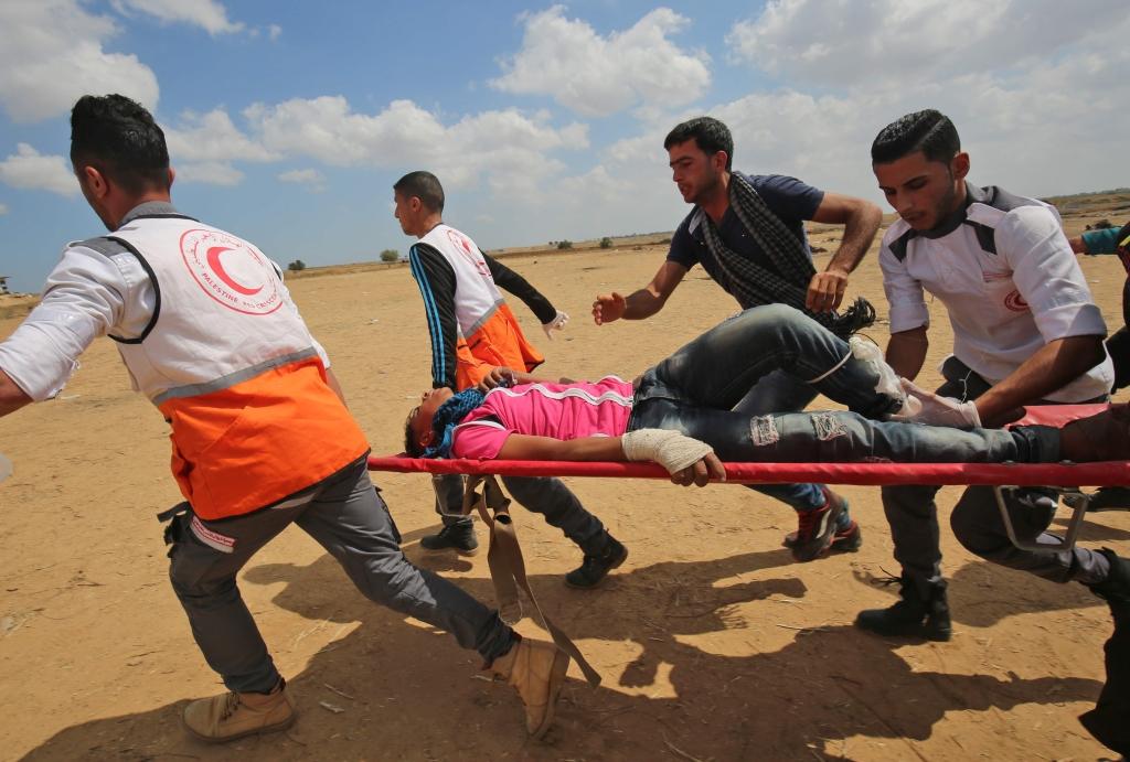 مسعفو الهلال الأحمر الفلسطيني ينقلون جريحاً ( أ ف ب)