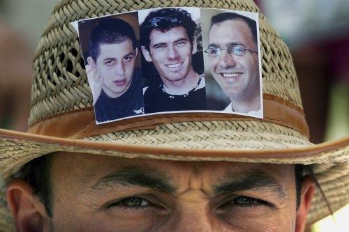 إسرائيليّ يحمل على قبّعته صور الأسيرين لدى حزب الله إيهود غولدفاسر وإلداد ريغيف، إضافة إلى جلعاد شاليط الذي أسر في قطاع غزة