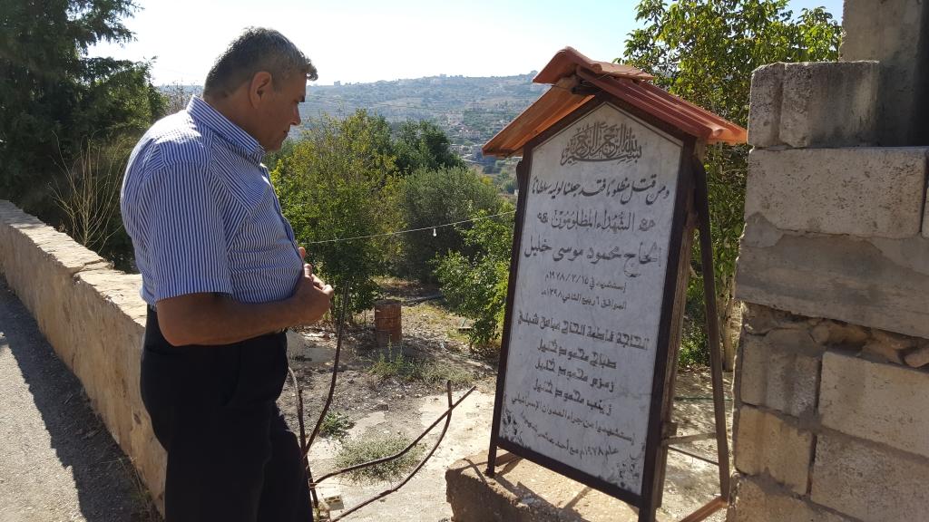 أبو توفيق حيدر أمام لوحة شهداء قريته