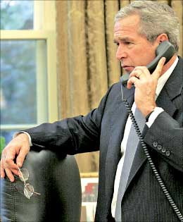 بوش يجري مكالمة هاتفية في مكتبه البيضاوي في واشنطن أمس (إي بي إيه)