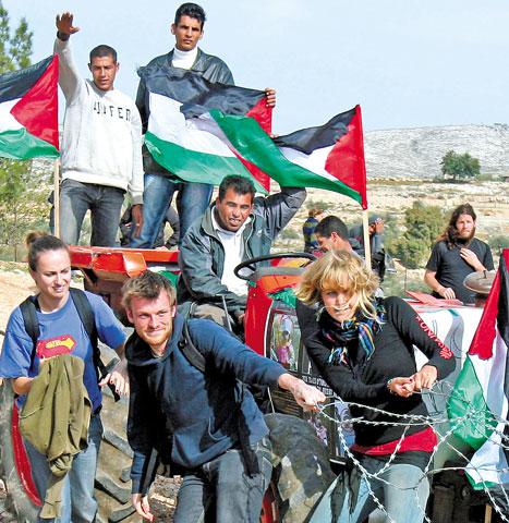 ناشـطو سـلام أجانـب وفلسطينيـون يسـحبون شـريطاً شـائكاً خـلال احتجـاج على جــدار الفصـل العنصـري في قريـة