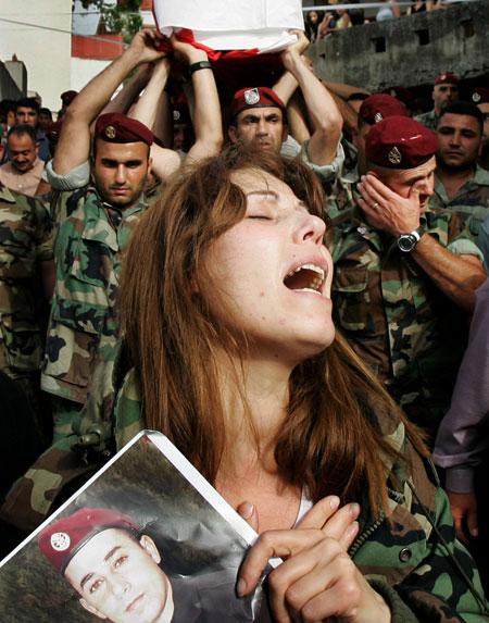 أمل تبكي شقيقها الجندي الشهيد حنّا فاهمة خلال تشييعه في بلدة رحبة العكارية أمس (بن كورتيس - أ ب)
