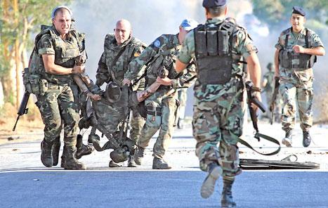 جنود إسبان ينقلون جثة زميلهم في سهل الدردارة أمس (علي ضيا - أ ف ب)