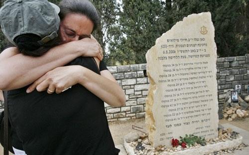 إسرائيليتان تتعانقان قرب نصب تذكاري لجنود الاحتياط الذين قتلوا خلال حرب تموز (أرشيف - رويترز)