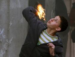 فتى فلسطيني يلقي بزجاجة حارقة على جنود الاحتلال عند حاجز قلنديا أمس (عباس موماني ـ أ ف ب)