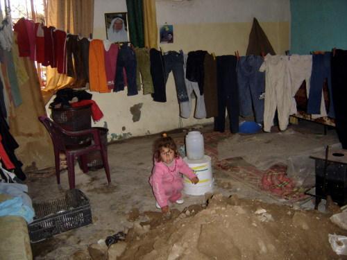 طفلة تلهو قرب كومة تراب داخل منزلها في عيتا الشعب