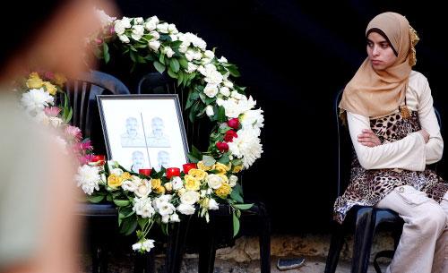 نوال الجندي إلى جانب صورة عمها أحمد التي وضعت في شارع الحمراء أمس (مروان طحطح)