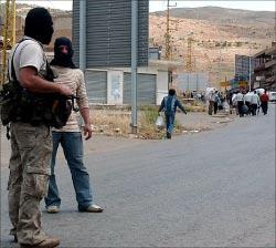 مسلحون موالون للسلطة عند نقطة المصنع يراقبون عبور مواطنين الى سوريا سيراً على الاقدام (أ ف ب)