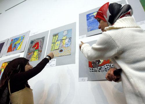 زهراء تشير إلى لوحتها الفائزة ( مروان طحطح)
