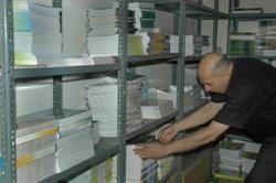 يجمع رزم الكتب تمهيداً لإرسالها إلى المدارس