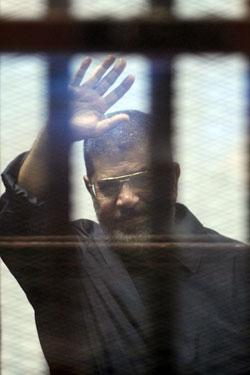 قررت جامعة الزقازيق أمس عزل محمد مرسي وإنهاء خدمته كأستاذ في الجامعة ــ الصورة خلال محاكمته في قضية التخابر مع قطر (آي بي ايه)