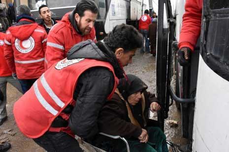 في ثلاثة «هنغارات» استُقبل الأهالي قبل نقلهم نحو حسياء في ريف حمص  (أ ف ب)