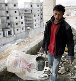 فلسطيني يعمل في ورشة بناء مستوطنة جديدة في جبل أبو غنيم أمس (إليانا أبونتي - رويترز)