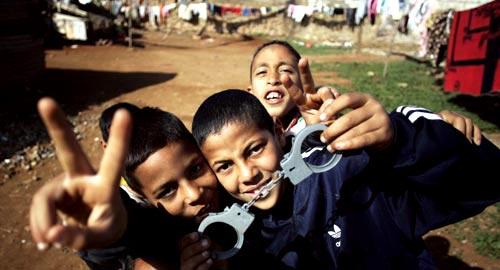 أطفال مغاربة يلهون بأصفاد الشرطة في الرباط (رافاييل مارشانت - رويترز)