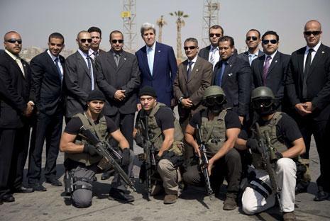 كيري يلتقط صورة مع فريق الأمن الخاص قبيل أن يستقل طائرته المتوجهة من القاهرة إلى باريس (أ ف ب)