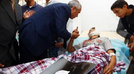 """رئيس حكومة """"الإنقاذ الوطني"""" عمر الحاسي خلال زيارته جرحى اشتباكات طرابلس أول من أمس (أ ف ب)"""