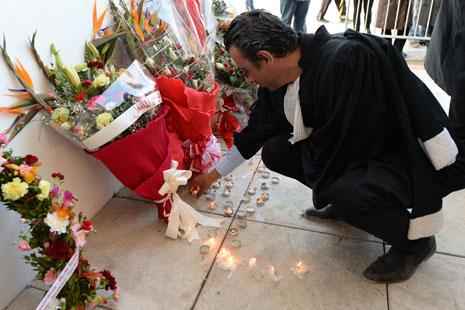 قاض يضع الورود أمام المتحف (أ ف ب)