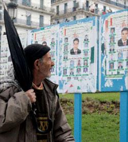 مواطن جزائري ينظر إلى الملصقات الانتخابية (رويترز)