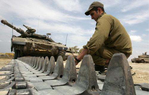 جندي إسرائيلي يصلح سلاسل دبّابة معطَّلة على الحدود مع غزّة (جاك غويز ــ أ ف ب)
