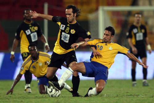لاعب قطر الإيراني علي كريمي بين لاعبين من الغرافة في المرحلة الماضية (كريم جعفر ـ أ ف ب)
