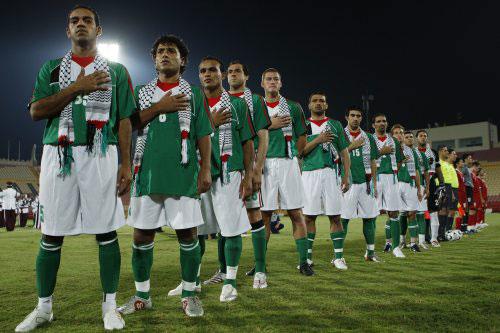 لاعبو المنتخب الفلسطيني واقفين لنشيدهم الوطني وسط الحصار (فادي الاسعد ـ رويترز)